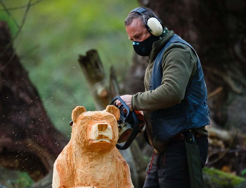 Shaun Gilbert artist and sculptor at work carving a chainsaw wooden bear near Norwich